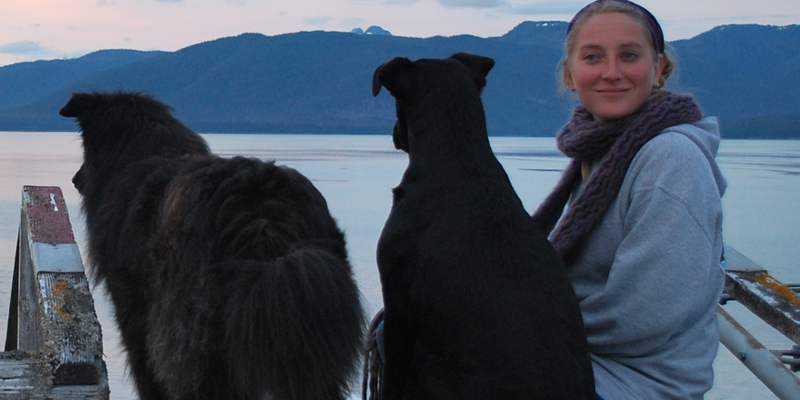 Student by the water with her dogs