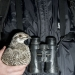 A sage grouse held tucked under the arm of person wearing a dark weather resistant jacket